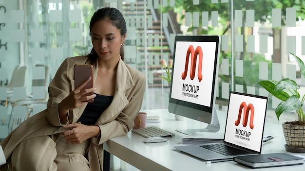 Porträt der unternehmerin mit smartphone mit desktop-modell