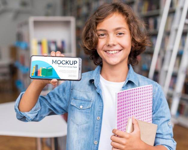 Porträt des jungen in der bibliothek, der modell telefon zeigt
