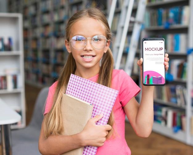 Porträt des mädchens in der bibliothek, die modell-telefon zeigt