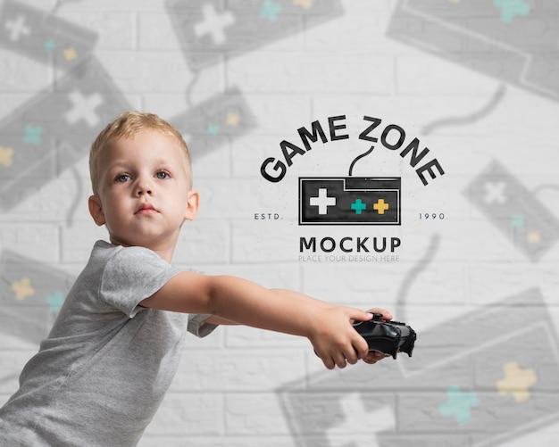 Porträt des niedlichen jungen, der auf konsole spielt
