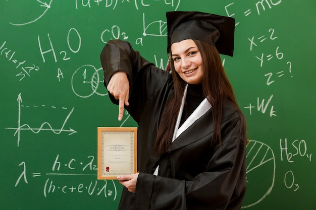 Porträt des studenten, der auf diplom zeigt