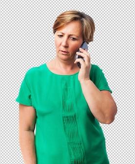 Porträt einer besorgten reifen frau, die am telefon spricht