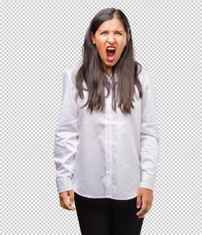 Porträt einer jungen inderin, die wütend schreit, ausdruck von wahnsinn und geistiger instabilität, offenem mund und halb geöffneten augen