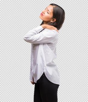 Porträt einer jungen indischen frau mit den rückenschmerzen wegen des arbeitsstresses, müde und scharfsinnig