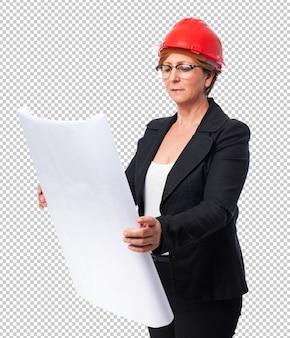 Porträt einer reifen architektenfrau, die ein flugzeug hält