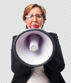 Porträt einer reifen geschäftsfrau, die mit einem megaphon schreit
