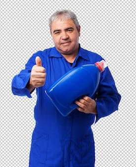 Porträt eines mechanikers, der eine ölflasche hält