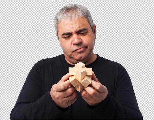 Porträt eines reifen mannes, der versucht, ein puzzlespiel zu lösen
