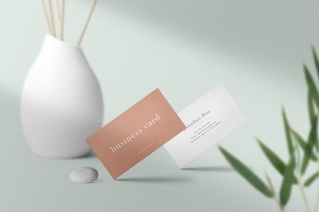 Premium-sauberes minimalistisches visitenkartenmodell auf dem boden mit vase und licht.
