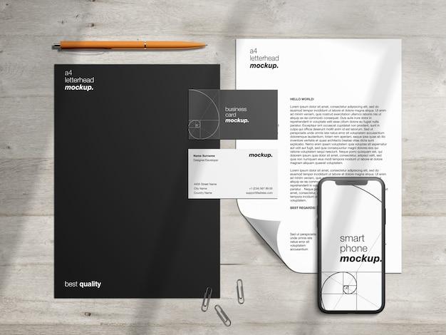 Professionelle mockup-vorlage für unternehmensidentitätsbriefpapier und szenenersteller mit briefkopf, visitenkarten und smartphone