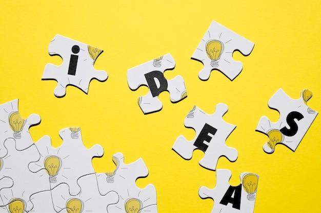 Puzzle-konzept mit buchstaben und glühbirnen