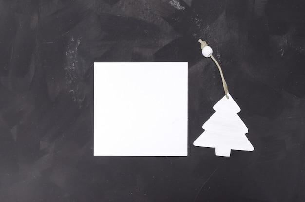 Quadratische karte des weihnachtsminimalistic modells auf schwarzer tabelle