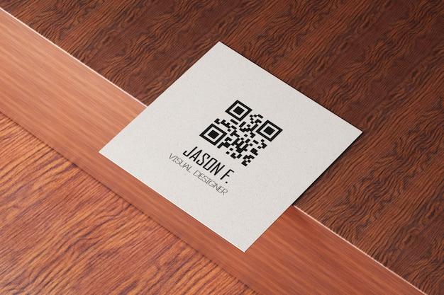 Quadratisches papier-visitenkartenmodell auf holztisch