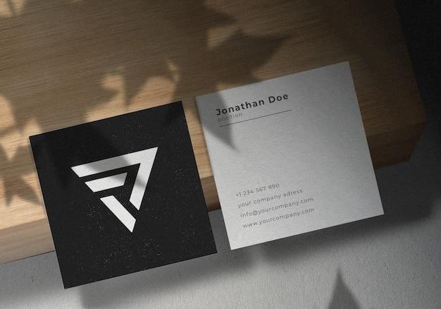 Quadratisches visitenkarten-modelldesign auf holzbrett