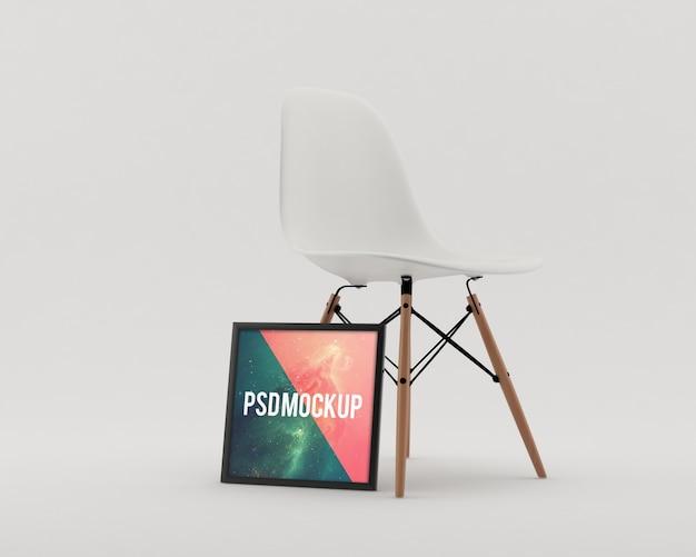 Rahmen neben einem weißen stuhl mock up