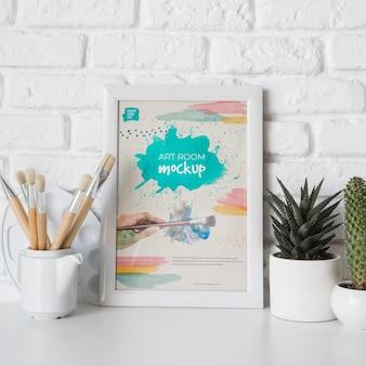 Rahmen neben pflanze auf schreibtisch