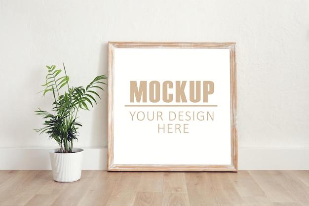 Rahmen, poster mit holzrahmen. leerer rahmen, der auf dem holzboden mit einer grünen pflanze steht. freier speicherplatz für ihr bild oder ihren text, platz kopieren. minimalistisches design.