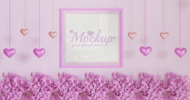 Rahmenmodell des weißen quadrats auf rosa wand mit rosa blattpflanzen und herzförmiger hängender dekoration