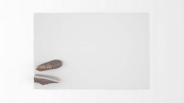 Realistischer weißer teppich mit einem paar schuhen auf draufsicht