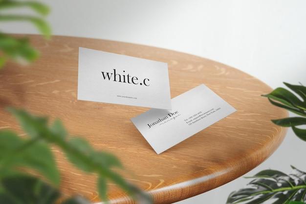 Reinigen sie das minimale visitenkartenmodell auf dem oberen tisch mit blättern