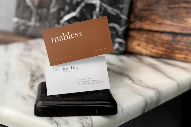 Reinigen sie das minimale visitenkartenmodell auf dem tisch und dem hellen schatten.