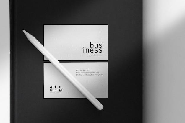 Reinigen sie minimales visitenkartenmodell auf schwarzem buch und digitalem bleistift