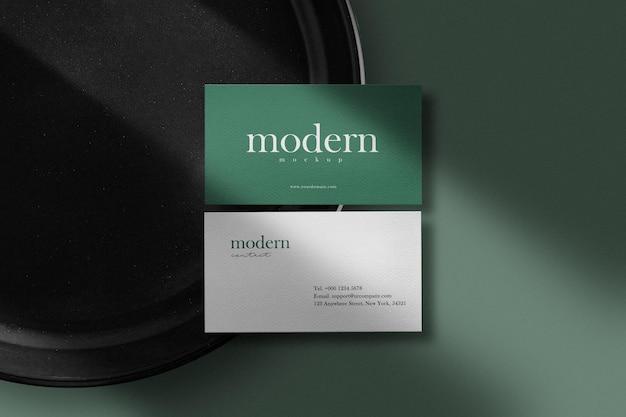Reinigen sie minimales visitenkartenmodell auf schwarzem teller mit schatten