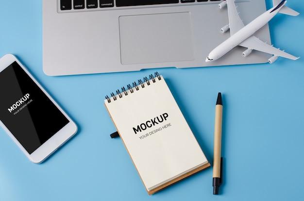 Reisebuchung mit laptop-, notizbuch-, smartphone- und flugzeugmodell auf blauer tabelle.