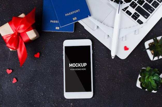 Reisebuchung mit smartphone, flugzeugmodell, laptop, pässen und geschenkbox