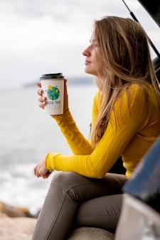 Reisender, der eine nachgemachte tasse kaffee hält