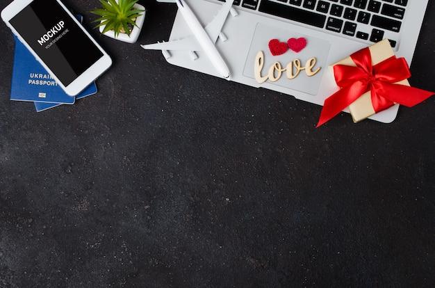 Reiseplanung mit smartphone, flugzeugmodell, laptop, pässen und geschenkbox