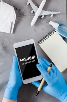 Reiseplanungskonzept, coronavirus und quarantäne. hände in einweghandschuhen halten das smartphone und schreiben in das notizbuch. machen sie sich mit dem speicherplatz vertraut. flugzeugmodell, gesichtsmaske und händedesinfektionsspray.