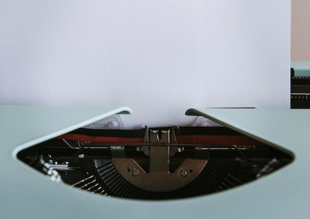 Retro-minze-schreibmaschine mit einem leeren weißen papiermodell