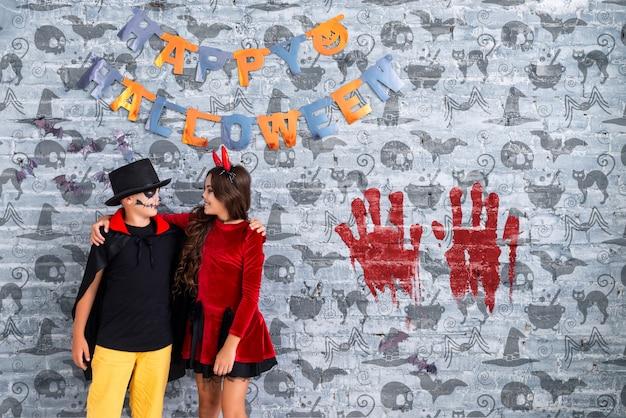 Riesenaufnahme von den geschwistern, die sich halten und glückliches halloween wünschen