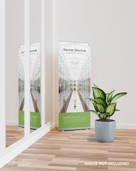 Rollen sie das banner-modell mit einer pflanze neben dem großen glas auf