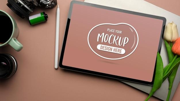 Rosa kreativer arbeitsbereich mit digitaler tablet-laptop-tulpenblumenkamera und kaffeetasse