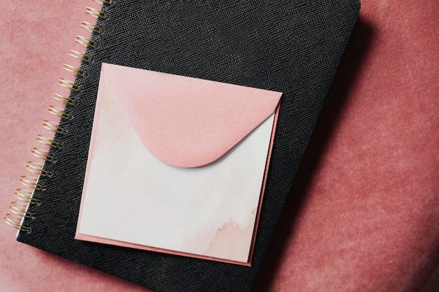 Rosa umschlagmodell auf einem schwarzen notizbuch