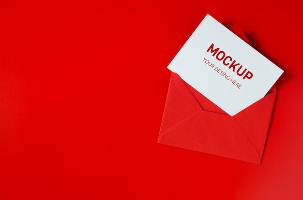 Roter umschlag mit leerem weißbuch. valentinstag hintergrund. mock-up liebesbrief.