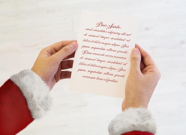 Santa claus hände halten ein briefmodell