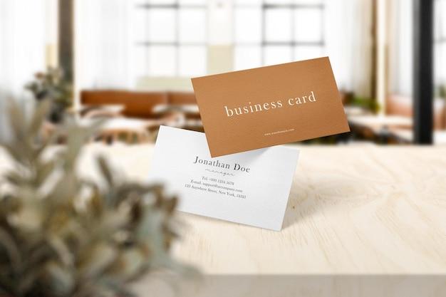 Sauberes minimales visitenkartenmodell auf dem oberen tisch im café mit blättern