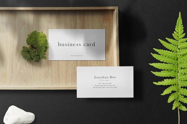 Sauberes minimales visitenkartenmodell auf holzplatte mit grünem moos.