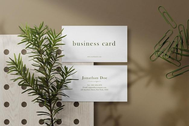 Sauberes minimales visitenkartenmodell auf holzplatte mit pflanzen- und büroklammern