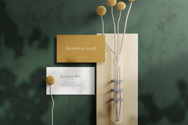 Sauberes minimales visitenkartenmodell auf marmorstruktur mit ästen und pflanzen