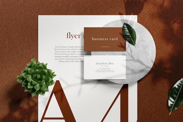 Sauberes minimales visitenkartenmodell auf papier a4 mit blättern und pflanzen