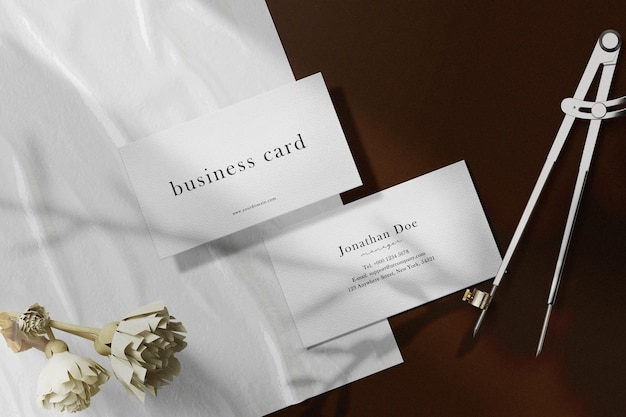 Sauberes minimales visitenkartenmodell auf papier mit trockenen pflanzen