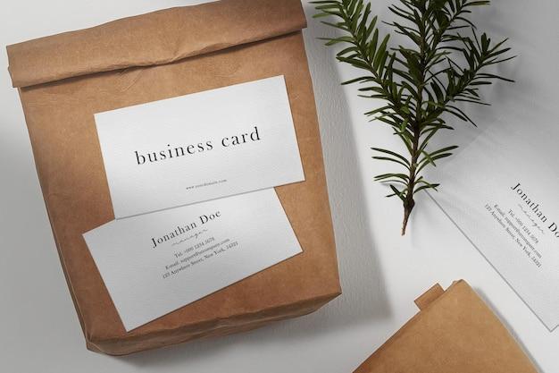 Sauberes minimales visitenkartenmodell auf papiertüte mit nadelbaum
