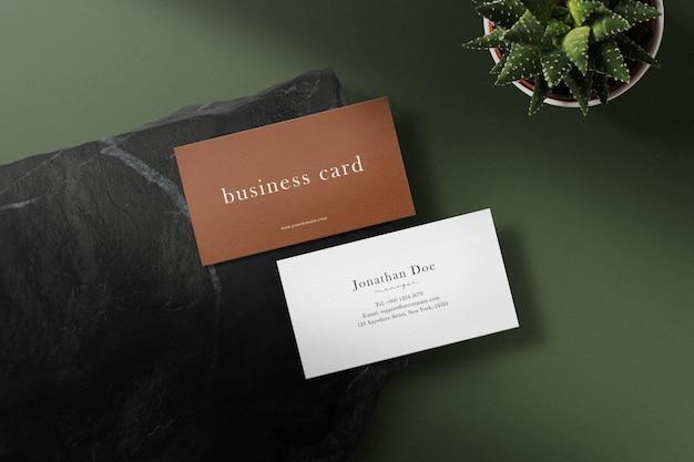 Sauberes minimales visitenkartenmodell auf schwarzem stein mit blatt