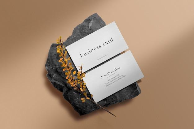 Sauberes minimales visitenkartenmodell auf schwarzem stein mit gelber pflanze