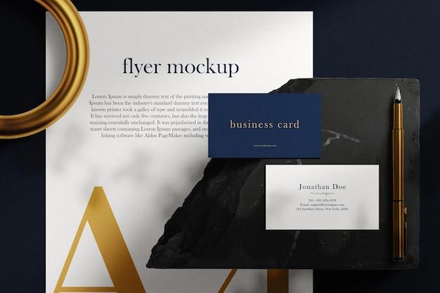 Sauberes minimales visitenkartenmodell auf schwarzem stein und papier a4 mit goldenem stifthintergrund. psd-datei.