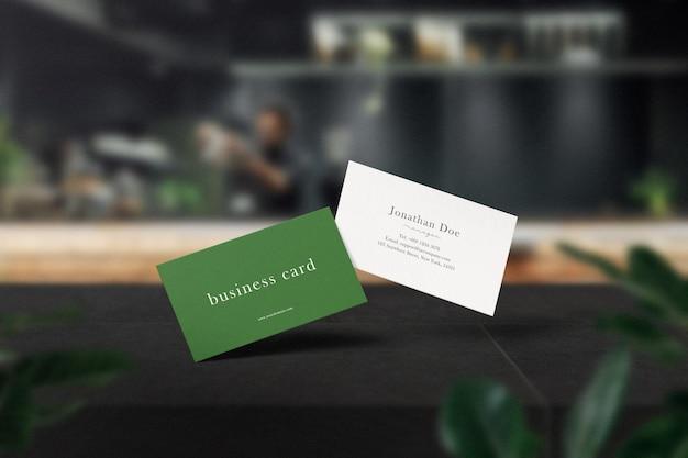 Sauberes minimales visitenkartenmodell auf schwarzem tisch im café mit blättern